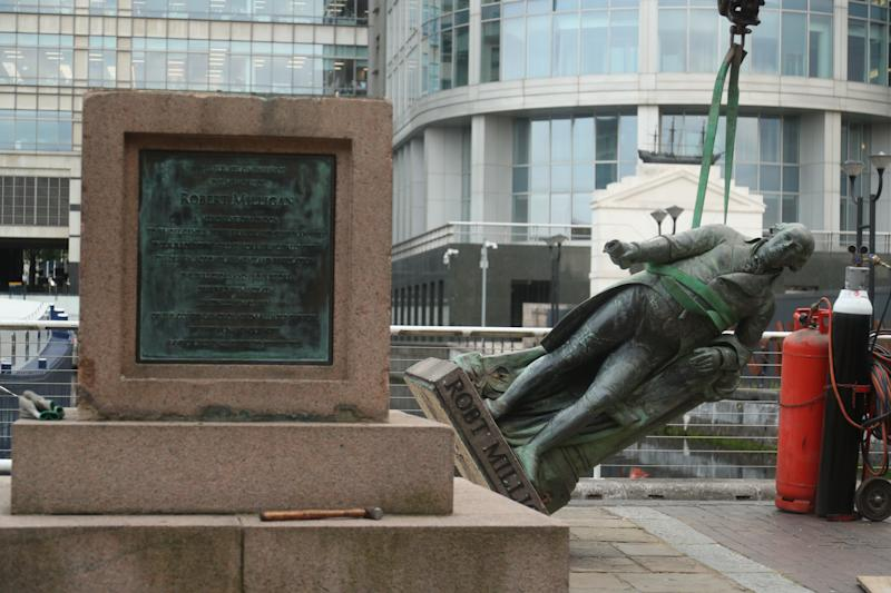 Workers prepare to take down a statue of slave owner Robert Milligan at West India Quay, east London as Labour councils across England and Wales will begin reviewing monuments and statues in their towns and cities, after a protest saw anti-racism campaigners tear down a statue of a slave trader in Bristol.