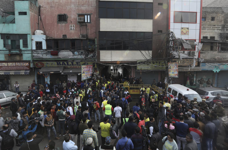 Locals and media person stand outside the site of a fire in an alleyway, tangled in electrical wire and too narrow for vehicles to access, in New Delhi, India, Sunday, Dec. 8, 2019. Dozens of people died on Sunday in a devastating fire at a building in a crowded grains market area in central New Delhi, police said. (AP Photo/Manish Swarup)