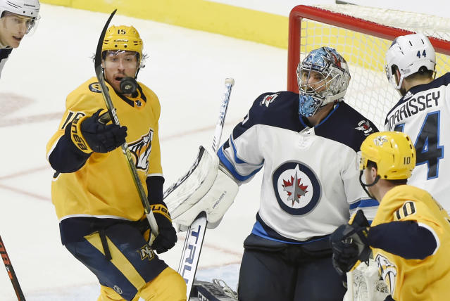 Nashville Predators right wing Craig Smith (15) watches the puck after a shot deflected off Winnipeg Jets goaltender Connor Hellebuyck (37) during the third period of an NHL hockey game Thursday, Jan. 17, 2019, in Nashville, Tenn. The Jets won 5-1. (AP Photo/Mark Zaleski)