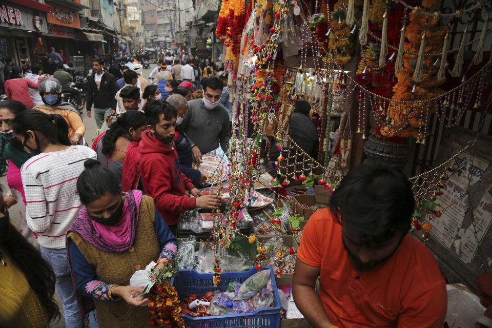 Indians wearing face masks as a precautionary measure against the coronavirus shop during Diwali, the Hindu festival of lights, in Jammu, India, Saturday, Nov. 14, 2020. (AP Photo/ Channi Anand)