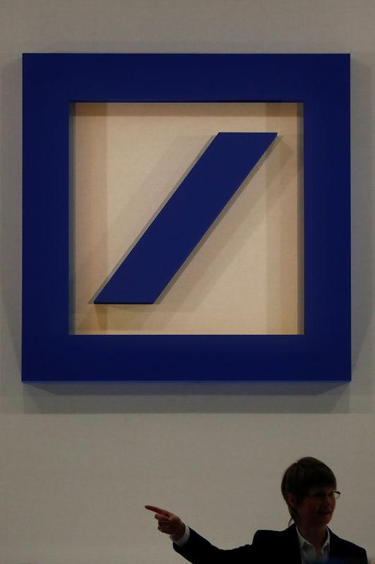 A person is silhouetted next to the Deutsche Bank's logo prior to the bank's annual meeting in Frankfurt