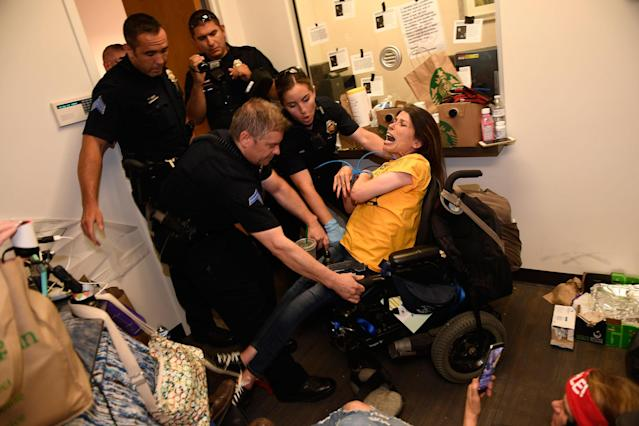 """<p>JUN. 29, 2017 – Dawn Russell gets arrested by Denver police officers after refusing the vacate the offices of Senator Cory Gardner in Denver, Colorado. A handful of people, all of whom are with ADAPT, held a sit-in for 58 hours in the tiny front lobby space in the office of Colorado Senator Cory Gardner. They are asking the senator to vote against the new health care bill. As they were arrested protesters chanted """"I would rather go to jail than die without Medicaid."""" ADAPT is a national grass-roots community that organizes disability rights activists to engage in nonviolent direct action, including civil disobedience, to assure the civil and human rights of people with disabilities to live in freedom. (Photo: Helen H. Richardson/The Denver Post via Getty Images) </p>"""