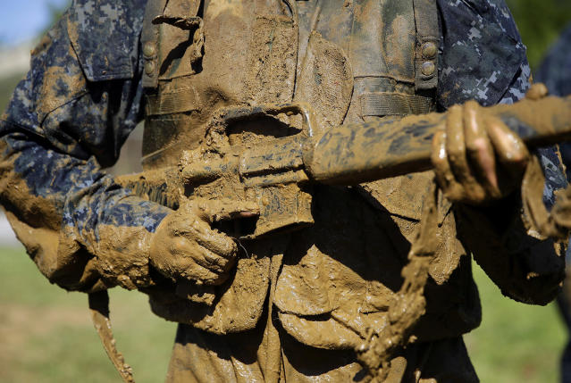 "<p>A first-year midshipman, known as a ""plebe,"" carries a dummy rifle covered in mud during Sea Trials, a day-long training exercise that caps off their plebe year at the U.S. Naval Academy in Annapolis, Md., Tuesday, May 16, 2017. (Photo: Patrick Semansky/AP) </p>"