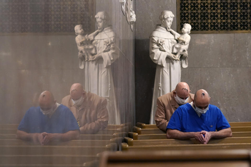 Sanar Yokhana, foreground, and Richard Lewandowski pray in front of a statue of St. Anthony during an Ash Wednesday service at the St. Aloysius Catholic Church, Wednesday, Feb. 17, 2021, in Detroit. The ashes, a symbol of penance, are made from palm leaves used in last year's Palm Sunday liturgy and were sprinkled on their head. The sprinkling, because of the pandemic, is a departure from the usual practice of making the sign of the cross on the forehead and follows an ancient method still common in parts of the world today. (AP Photo/Carlos Osorio)