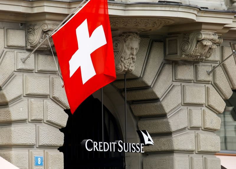 FILE PHOTO: Switzerland's national flag flies above the logo of Swiss bank Credit Suisse in Zurich