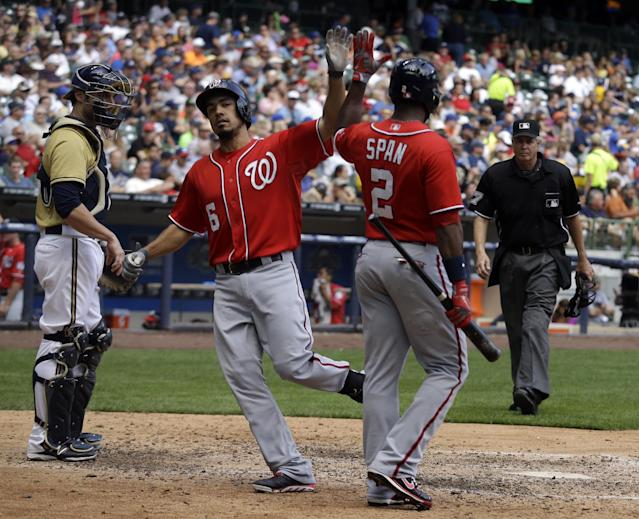 Washington Nationals' Anthony Rendon (6) is congratulated by teammate Scooter Gennett (2) after Rendon hit a home run during the seventh inning of a baseball game against the Milwaukee Brewers Sunday, Aug. 4, 2013, in Milwaukee. At left is Milwaukee Brewers catcher Jonathan Lucroy. (AP Photo/Morry Gash)