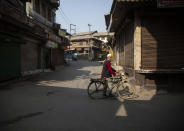 An elderly Kashmiri man rides a bicycle past closed shops during a strike called by separatists in Srinagar, Indian controlled Kashmir, Saturday, Oct. 31, 2020. Kashmir's main separatist grouping called the strike to protest new land laws that India enacted on Tuesday, allowing any of its nationals to buy land in the region. Pro-India politicians in Kashmir have also criticized the laws and accused India of putting Kashmir's land up for sale. The move exacerbates concerns of Kashmiris and rights groups who see such measures as a settler-colonial project to change the Muslim-majority region's demography. (AP Photo/Mukhtar Khan)