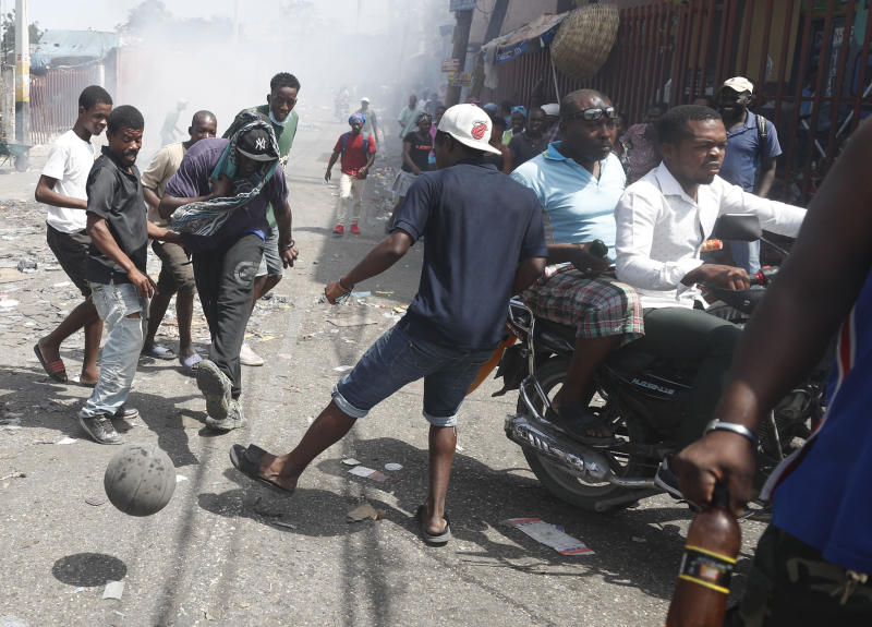 Demonstrators play soccer with a basketball during an anti-government protest on a street in Port-au-Prince, Haiti, Friday, Oct. 11, 2019. Protesters burned tires and spilled oil on streets in parts of Haiti's capital as they renewed their call for the resignation of President Jovenel Moïse just hours after a journalist was shot to death. (AP Photo/Rebecca Blackwell)