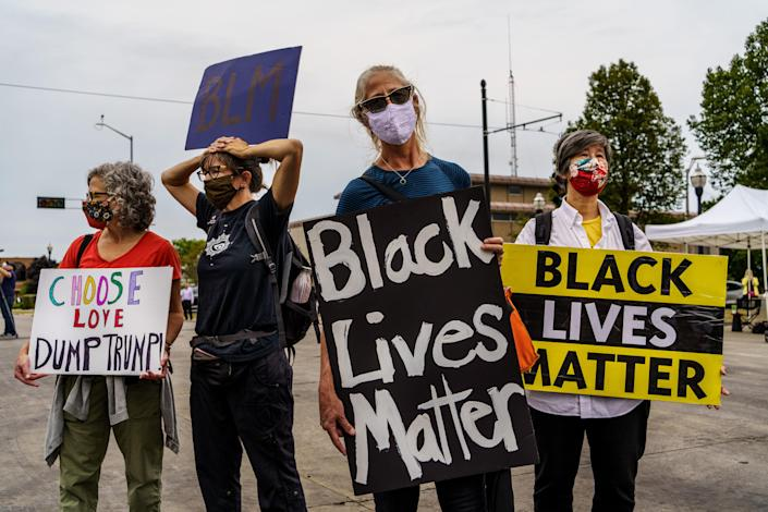 Demonstrators hold signs in front of the Kenosha Courthouse on September 01, 2020 in Kenosha, Wisconsin. (Kerem Yucel/AFP via Getty Images)
