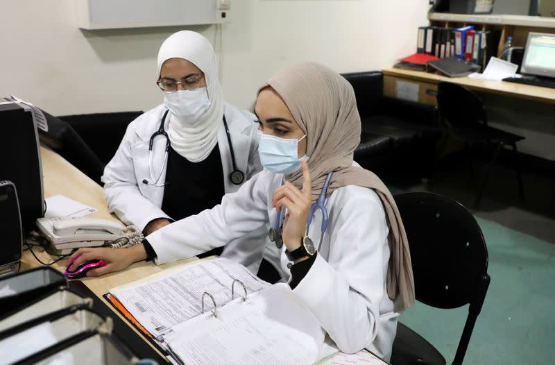 Israa Seblani, a Lebanese doctor and the bride who was caught up in the last year's Beirut port blast during a wedding photoshoot, gestures as she works at Rafik Hariri University Hospital, in Beirut