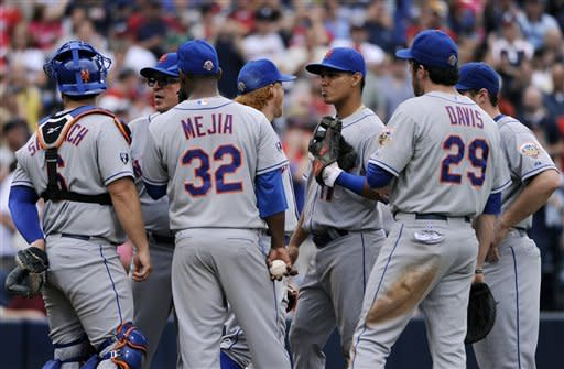 The New York Mets surround starting pitcher Jenrry Mejia during the fifth inning of their baseball game against the Atlanta Braves at Turner Field Sunday, Sept. 30, 2012, in Atlanta. (AP Photo/David Tulis)