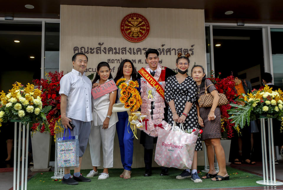 A university student poses for a group photo with family and friends ahead of a graduation ceremony at the Thammasat University, Friday, Oct. 30, 2020, in Bangkok, Thailand. (AP Photo/Sakchai Lalit)
