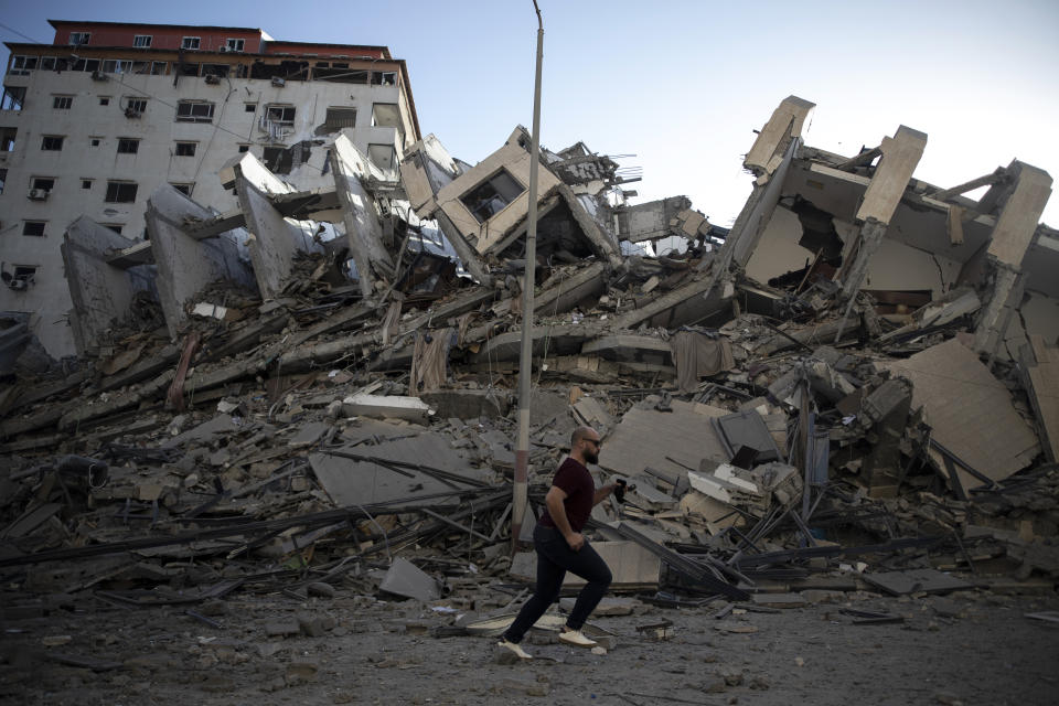 A Palestinian man passes by the remains of a building destroyed by Israeli airstrikes on Gaza City, Wednesday, May 12, 2021. Rockets streamed out of Gaza and Israel pounded the territory with airstrikes early Wednesday as the most severe outbreak of violence since the 2014 war took on many of the hallmarks of that devastating 50-day conflict, with no endgame in sight. (AP Photo/Khalil Hamra)