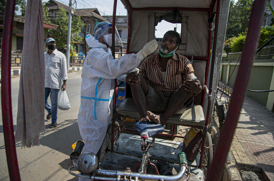 A health worker takes a nasal swab sample of a rickshaw driver during random testing for COVID-19 in a market in Gauhati, India, Friday, Oct. 16, 2020. India's coronavirus fatalities jumped by 895 in the past 24 hours, a day after recording the lowest daily deaths of 680 in nearly three months. The Health Ministry on Friday also reported 63,371 new cases in the past 24 hours, raising India's total to more than 7.3 million, second in the world behind the U.S. (AP Photo/Anupam Nath)