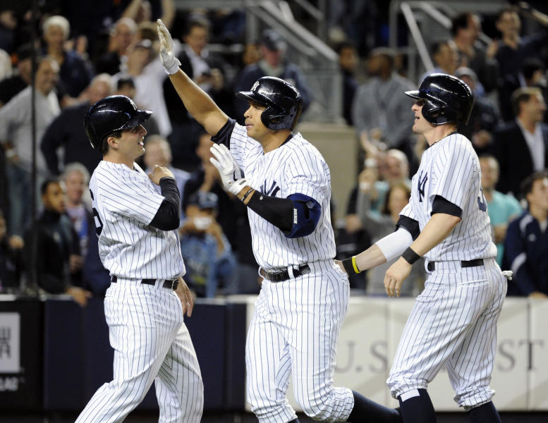 New York Yankees' Alex Rodriguez, center, celebrates with J.R. Murphy, left, and Brendan Ryan after Rodriguez hit a grand slam during the seventh inning of an interleague baseball game against the San Francisco Giants, Friday, Sept. 20, 2013, at Yankee Stadium in New York. (AP Photo/Bill Kostroun)