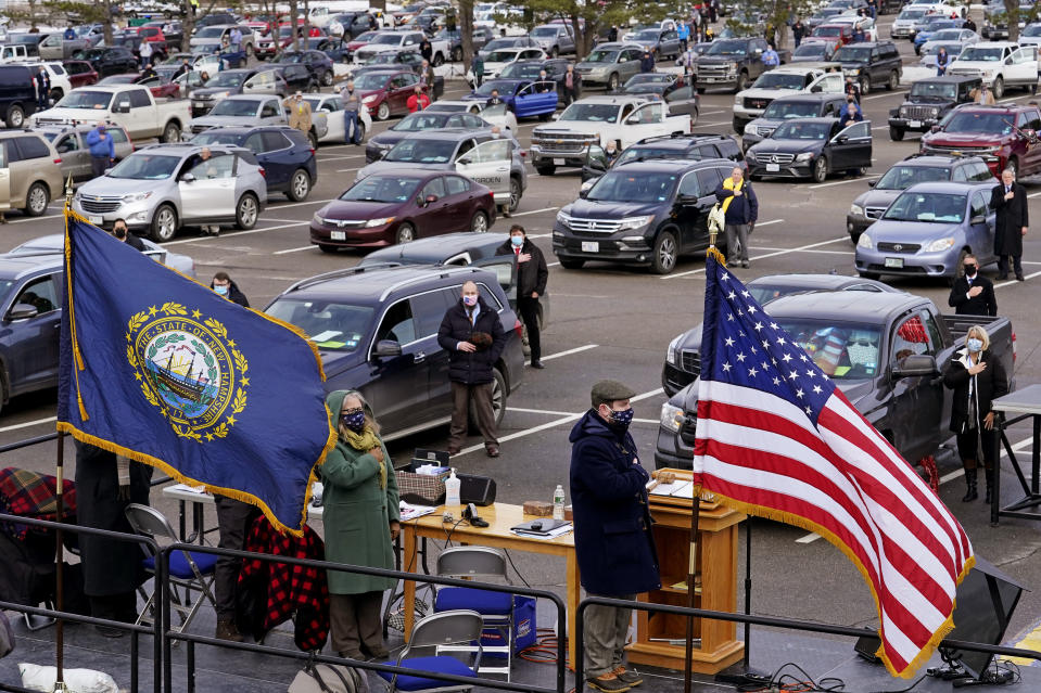 New Hampshire. State Representatives stand for the Pledge of Allegiance during an outdoor meeting of the New Hampshire House of Representatives in a parking lot, due to the COVID-19 virus outbreak, at the University of New Hampshire Wednesday, Jan. 6, 2021, in Durham, N.H. (AP Photo/Charles Krupa)