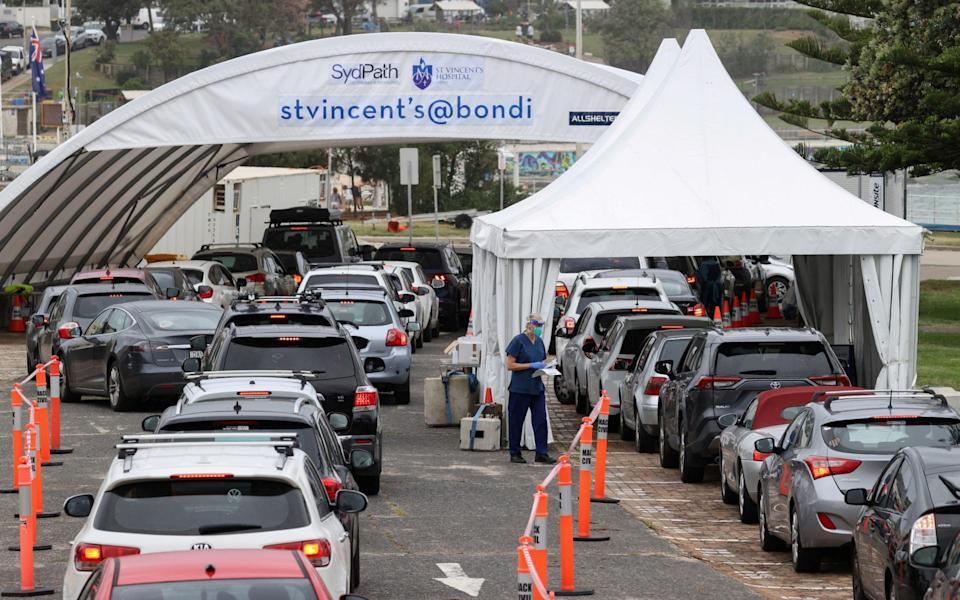 Vehicles queue as medical personnel administer tests at a drive-through COVID-19 testing centre in Sydney - Reuters
