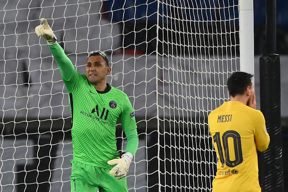 TOPSHOT - Paris Saint-Germain's Costa Rican goalkeeper Keylor Navas (L) celebrate after saving a penalty kick taken by Barcelona's Argentinian forward Lionel Messi during the UEFA Champions League round of 16 second leg football match between Paris Saint-Germain (PSG) and FC Barcelona at the Parc des Princes stadium in Paris, on March 10, 2021. (Photo by FRANCK FIFE / AFP) (Photo by FRANCK FIFE/AFP via Getty Images)