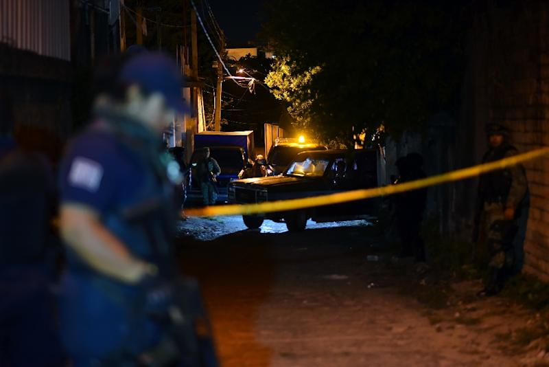 Police stand guard outside the setting of a party where 13 people were killed by unidentified gunmen (AFP Photo/ANGEL HERNANDEZ)