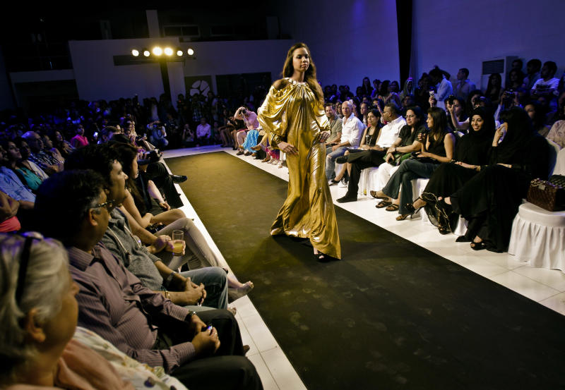 In this Saturday, March 16, 2013 photo, a model wears a modern style designer dress suitable for weddings, Ramadan feasts and Eid gatherings during a fashion show in Dubai, United Arab Emirates. Just a few years ago, Gulf Arab women usually only felt comfortable showing off their fashion sense at ladies-only parties or family gatherings. In public, at least in their home countries, the standard all-black abaya _ a simple floor-length covering and accompanying head scarf _ was the only culturally accepted option. But now a new generation of abaya designers are giving the traditional garment a twist with choices of fabric, designs and even some expensive bling to allow Gulf women a host of style options. (AP Photo/Kamran Jebreili)