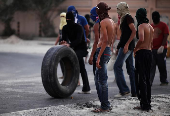 """A Bahraini anti-government protester rolls a tire towards burning tires on a street in the western village of Malkiya, Bahrain, Tuesday, Aug. 13, 2013. Inspired by the movement behind Egypt's military coup, pro-democracy activists in Bahrain are hoping to gain new momentum by calling for nationwide protests Wednesday. Authorities warned they will """"forcefully confront"""" any large demonstrations, raising fears of more violence in the strategic Gulf kingdom. (AP Photo/Hasan Jamali)"""
