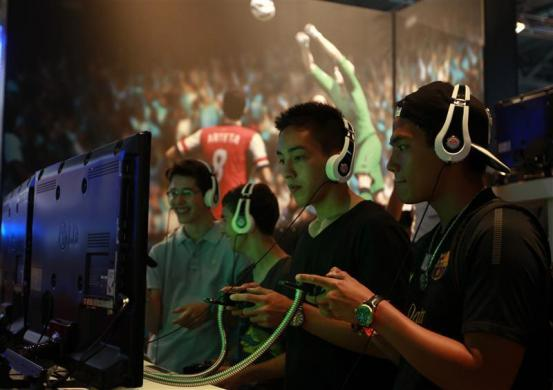 Visitors play FIFA13 during the Gamescom 2012 fair in Cologne August 16, 2012.