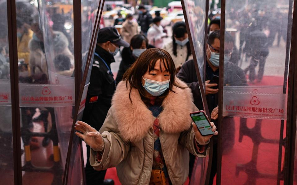 A woman wearing a face mask as a preventive measure against the Covid-19 coronavirus enters a shopping mall after showing her health code in Wuhan
