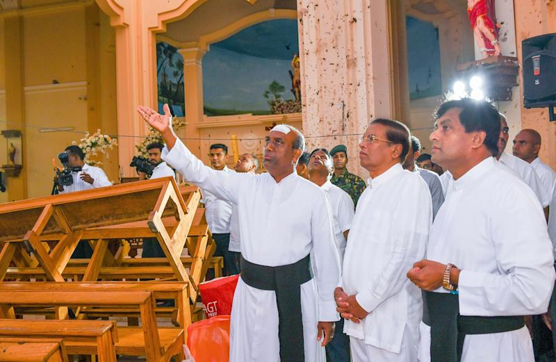 This handout photo taken and released by the Sri Lankan President's Office on April 23, 2019 shows President Maithripala Sirisena (second from the right), visiting St. Sebastian's church in Negombo, two days after a series of bomb attacks targeting churches and luxury hotels in Sri Lanka.