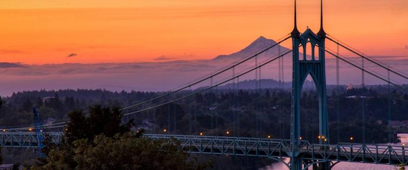 Gothic style arches tracery St Johns bridge and Mt Hood with beautiful sunrise in Portland, Oregon.