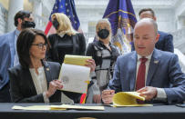 Utah Gov. Spencer Cox Cox, right and Lt. Gov. Deidre Henderson, left, were joined by activists and supporters of SB127 in the Capitol rotunda in Salt Lake City, Tuesday, April 6, 2021 for the ceremonial bill signing that will bring more oversight to the state's so-called troubled-teen industry. Rear from left, state Sen. Mike McKell, R-Spanish Fork, activist Jeff Netto, activist Paris Hilton, activist Caroline Lorson and Rep. Brady Brammer, R-Highland, look on. (Leah Hogsten/The Salt Lake Tribune via AP)
