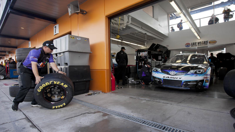 A pit crew member for Denny Hamlin rolls new tires into the garage before qualifying for the NASCAR Sprint Cup Series auto race, Friday, March 8, 2013 in Las Vegas. (AP Photo/Julie Jacobson)