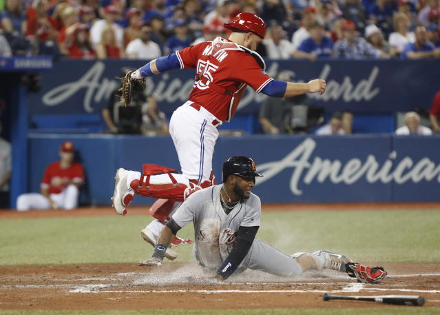 Detroit Tigers' Niko Goodrum, bottom, scores past Toronto Blue Jays' Russell Martin, top, during the fifth inning of a baseball game in Toronto, Sunday, July 1, 2018. (Mark Blinch/The Canadian Press via AP)