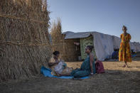 Ethiopian Amhara refugee 8-month pregnant Blaines Alfao Eileen, right, sits with Tigray refugee 25-year-old Lemlem Haylo Rada, holding her one-month old baby who was born on a street as she fled, at Um Rakuba refugee camp in Qadarif, eastern Sudan, Monday, Nov. 23, 2020. Tens of thousands of people have fled a conflict in Ethiopia for Sudan, sometimes so quickly they had to leave family behind. There is not enough to feed them in the remote area of southern Sudan that they rushed to. (AP Photo/Nariman El-Mofty)