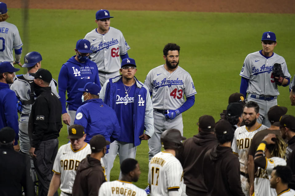 Members of the Los Angeles Dodgers and the San Diego Padres approach each other after San Diego Padres' Jorge Mateo was hit by a pitch from Los Angeles Dodgers starting pitcher Dennis Santana during the tenth inning of a baseball game Friday, April 16, 2021, in San Diego. (AP Photo/Gregory Bull)