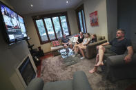The Wood family, from left, Ethan, Amanda, Lola, Ruby and David, watch television at home in Toronto, Canada, on Monday, July 12, 2021. With nearly 70% of its adult population receiving at least one dose of a COVID-19 vaccine, Canada has the world's highest vaccination rate and is now moving on to immunize children, who are at far lower risk of coronavirus complications and death. (AP Photo/Kamran Jebreili)
