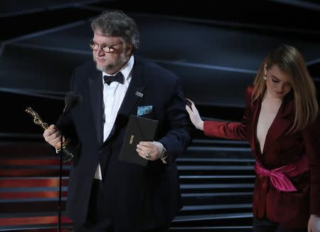 """90th Academy Awards - Oscars Show - Hollywood, California, U.S., 04/03/2018 - Guillermo del Toro accepts the Oscar for Best Director for """"The Shape of Water"""" from presenter Emma Stone (R). REUTERS/Lucas Jackson"""