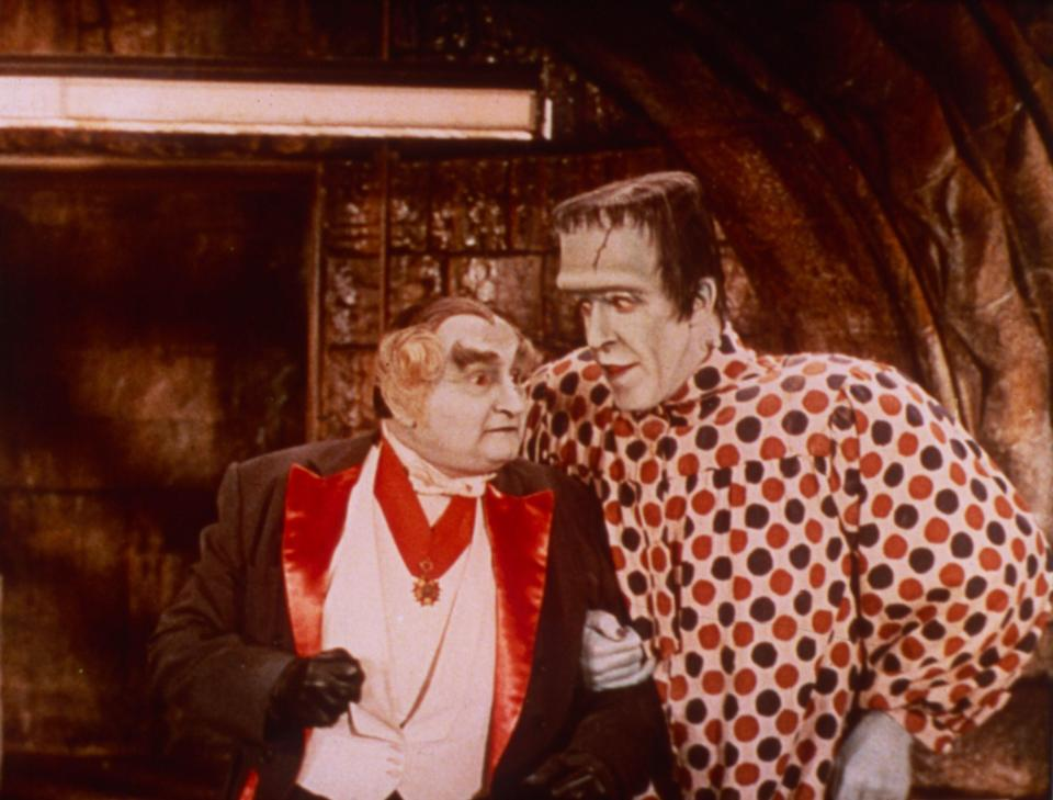 Al Lewis and Fred Gwynne stand next to each other dressed up as a vampire and Frankenstein