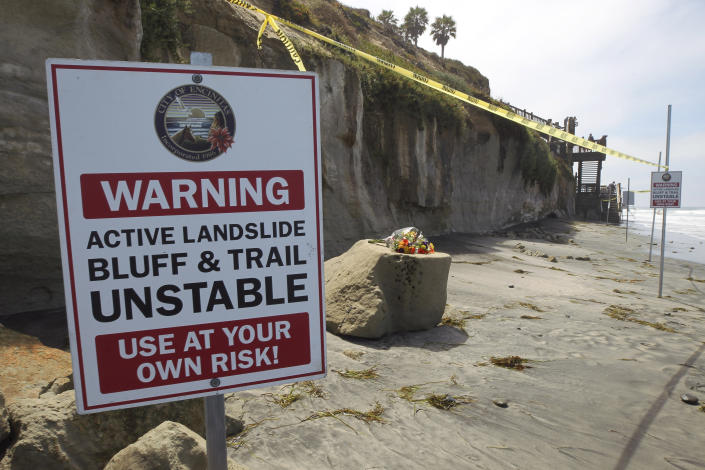 One of several warning signs is posted next to the sand rock debris left from Friday's sea cliff collapse that killed three people near the Grandview Beach access stairway in the beach community of Leucadia, Saturday, Aug. 3, 2019, in Encinitas, Calif. A bouquet of flowers has been placed one of the chunks of sand stone. Officials have reopened much of the Southern California beach on Saturday. (Hayne Palmour IV/The San Diego Union-Tribune via AP)