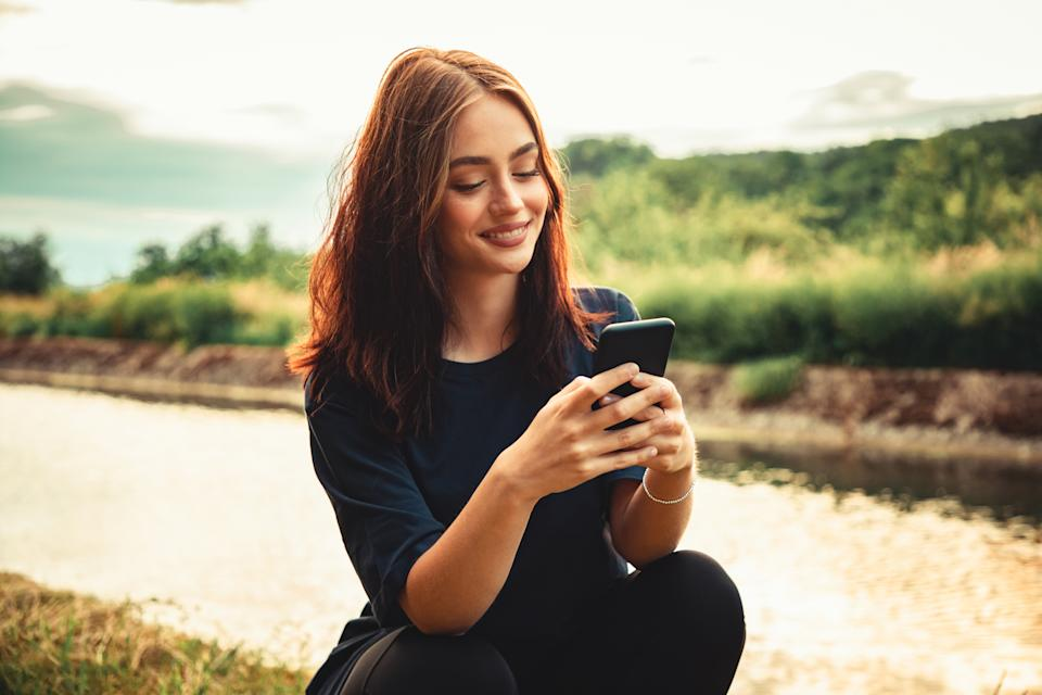 Happy smiling young woman sitting outdoors close to a river looking towards her mobile phone, writing messages with a bright happy smile. Real People Outdoor Youth Social Media Lifestyle.