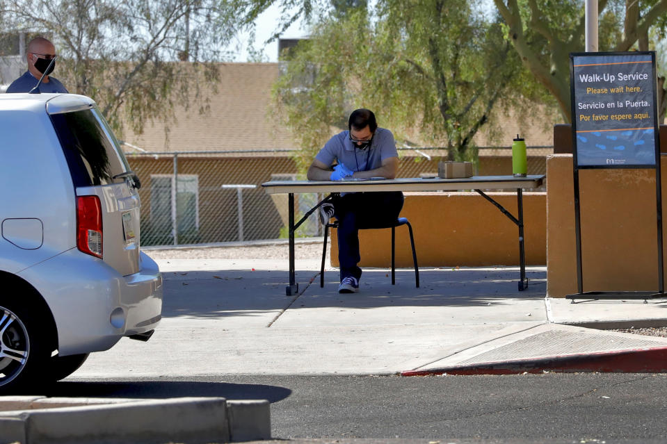 In this Thursday, June 18, 2020, photo, a man waits to check out books curbside from the Guadalupe library in Guadalupe, Ariz. As the coronavirus spreads deeper across America, it's ravaging through the homes and communities of Latinos from the suburbs of the nation's capital to the farm fields of Florida to the sprawling suburbs of Phoenix and countless communities in between. (AP Photo/Matt York)
