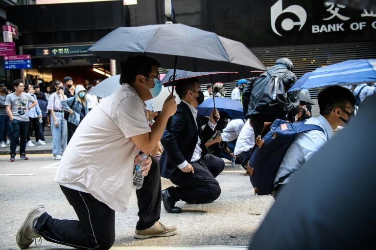 Office workers join the front lines after police fired tear gas during a flash mob protest in the Central district of Hong Kong (AFP Photo/ANTHONY WALLACE)