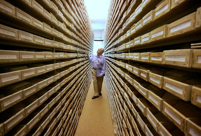 In this May 8, 2008 file picture Gary Mokotoff, a Jewish genealogist from New Jersey, takes a look at name registers at the International Tracing Service in Bad Arolsen, central Germany. (AP Photo/Michael Probst, file)