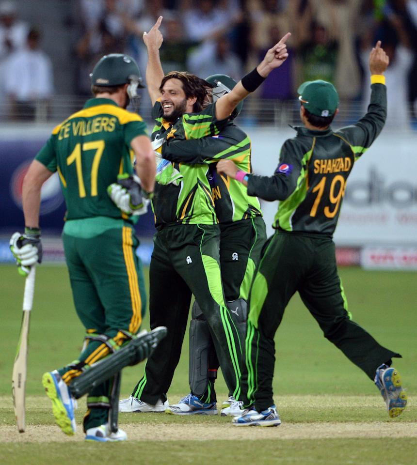 Pakistani bowler Shahid Afridi (C) celebrates with team-mates after taking South African cricketer Faf du Plessis (unseen) out for Leg Before Wicket during the second day-night international against South Africa in Dubai Cricket Stadium in Dubai on November 1, 2013. Pakistan were bowled out for 209 in their innings. South Africa lead the five-match series 1-0. AFP PHOTO/ ASIF HASSAN        (Photo credit should read ASIF HASSAN/AFP/Getty Images)
