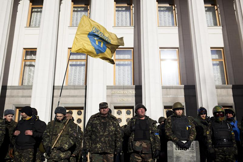 """Self defense volunteers line up outside the Parliament in Kiev, Ukraine, Monday, March 17, 2014. A referendum held in Crimea on Sunday was widely condemned by Western leaders who were planning to discuss economic sanctions to punish Russia on Monday. Ukraine's new government in Kiev called the referendum a """"circus"""" directed at gunpoint by Moscow.(AP Photo/David Azia)"""