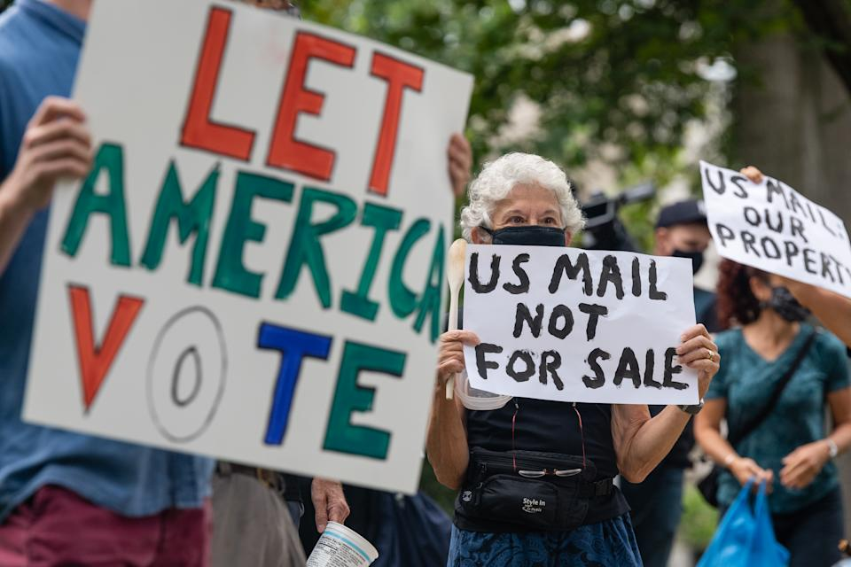 Demonstrators with Shut Down DC protest prepare to march to the home of Postmaster General Louis DeJoy in Washington, D.C., U.S., on Saturday, Aug. 15, 2020. (Eric Lee/Bloomberg via Getty Images)