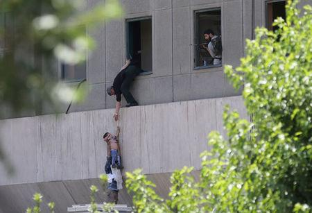 FILE PHOTO: A boy is evacuated during an attack on the Iranian parliament in central Tehran, Iran June 7, 2017. Omid Vahabzadeh/TIMA via REUTERS/File Photo via REUTERS