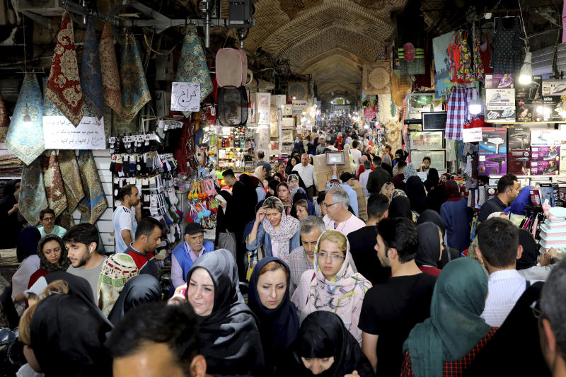 """People shop at the old main bazaar in Tehran, Iran, Tuesday, July 2, 2019. From an English-language teacher hoping for peace to an appliance salesman who applauded Donald Trump as a """"successful businessman,"""" all said they suffered from the economic hardships sparked by re-imposed and newly created American sanctions.  (AP Photo/Ebrahim Noroozi)"""