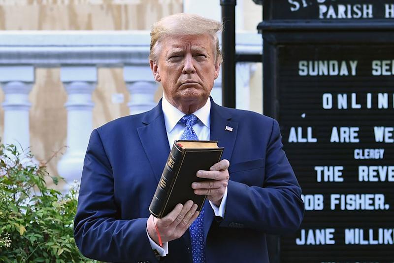 Pictured is US President Donald Trump posing for a photograph as he holds a bible outside the St John's Church, which was set alight amid George Floyd protests.