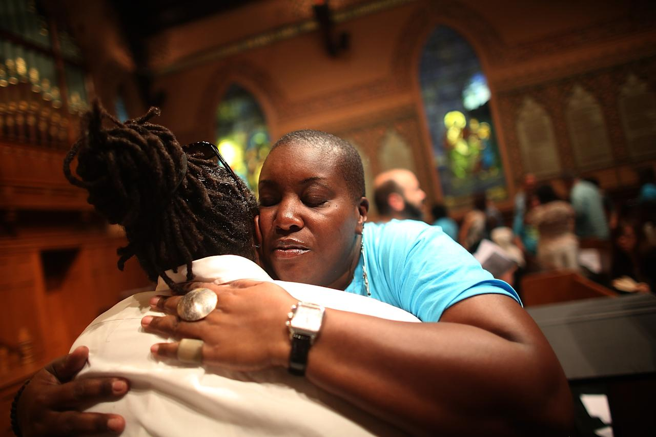 NEW YORK, NY - JULY 14: People hug during services at Middle Collegiate Church in Manhattan honoring Trayvon Martin on July 14, 2013 in New York City. George Zimmerman was acquitted of all charges in the shooting death of Martin July 13 and some congregants wore hoodies during the service to honor Martin. (Photo by Mario Tama/Getty Images)