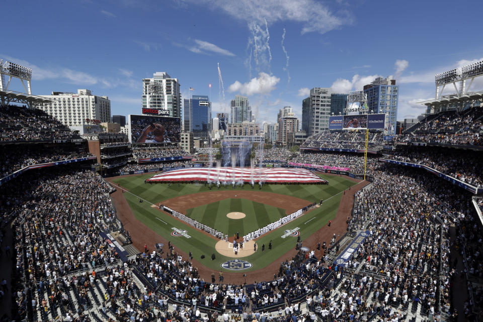 Players for the San Francisco Giants and the San Diego Padres stand during the singing of the national anthem before an opening day baseball game, Thursday, March 28, 2019, in San Diego. (AP Photo/Gregory Bull)